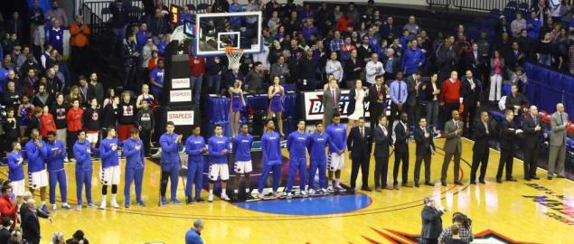 The DePaul Blue Demons men's basketball team standing for the National Anthem.