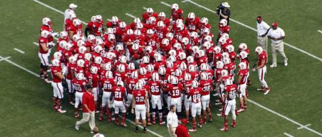 The NC State Wolfpack huddling during a game.