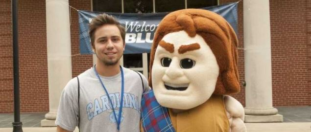 Presbyterian College's Scotty the Scotsman mascot posing with student in 2017.