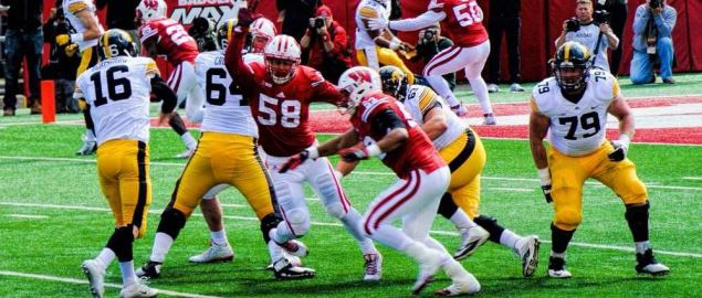 Iowa Hawkeyes trying to block a pass from the Badgers.